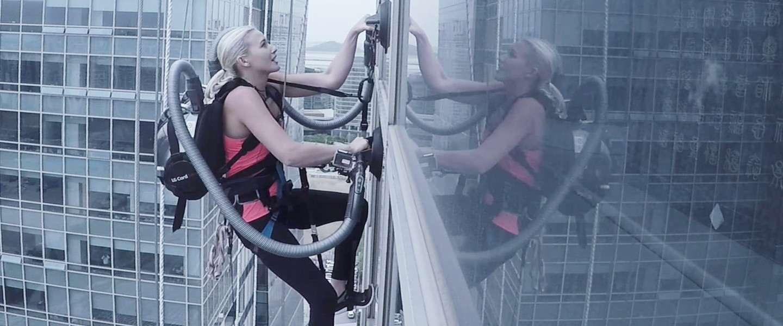 Spiderwoman beklimt wolkenkrabber met twee stofzuigers